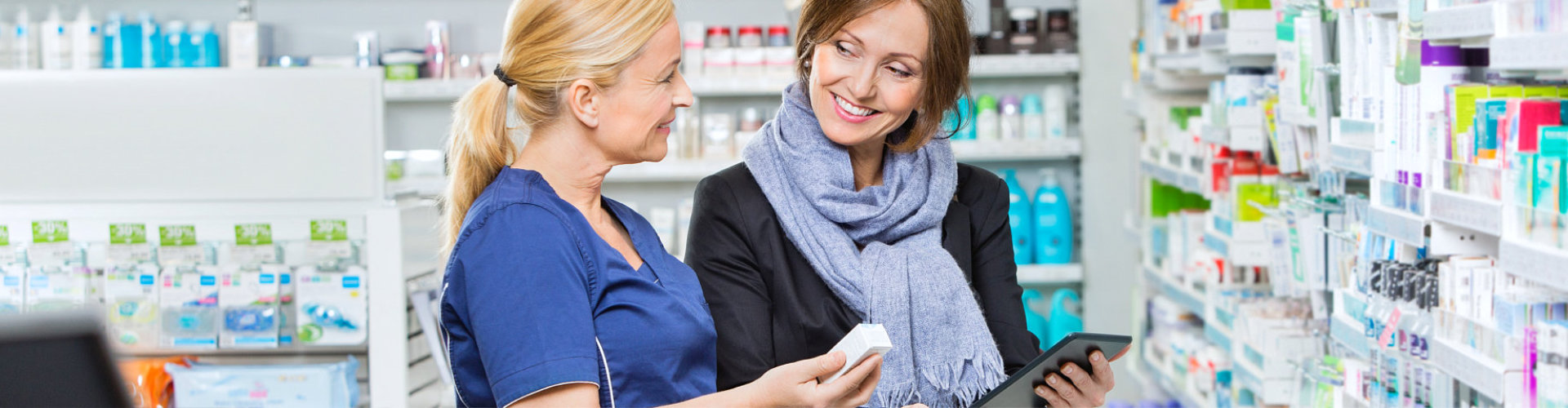 female pharmacist in blue uniform and female customer looking at each other
